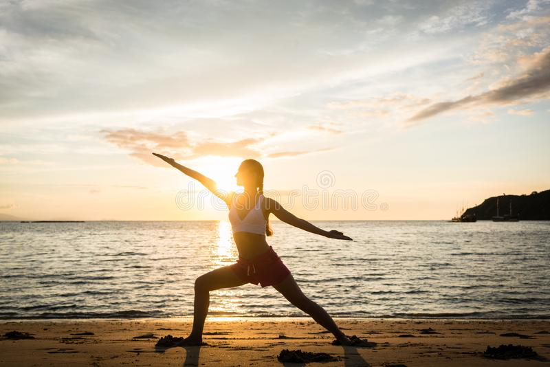 Download Silhouette Of A Fit Woman Practicing The Warrior Yoga Pose At Sunset Stock Photo