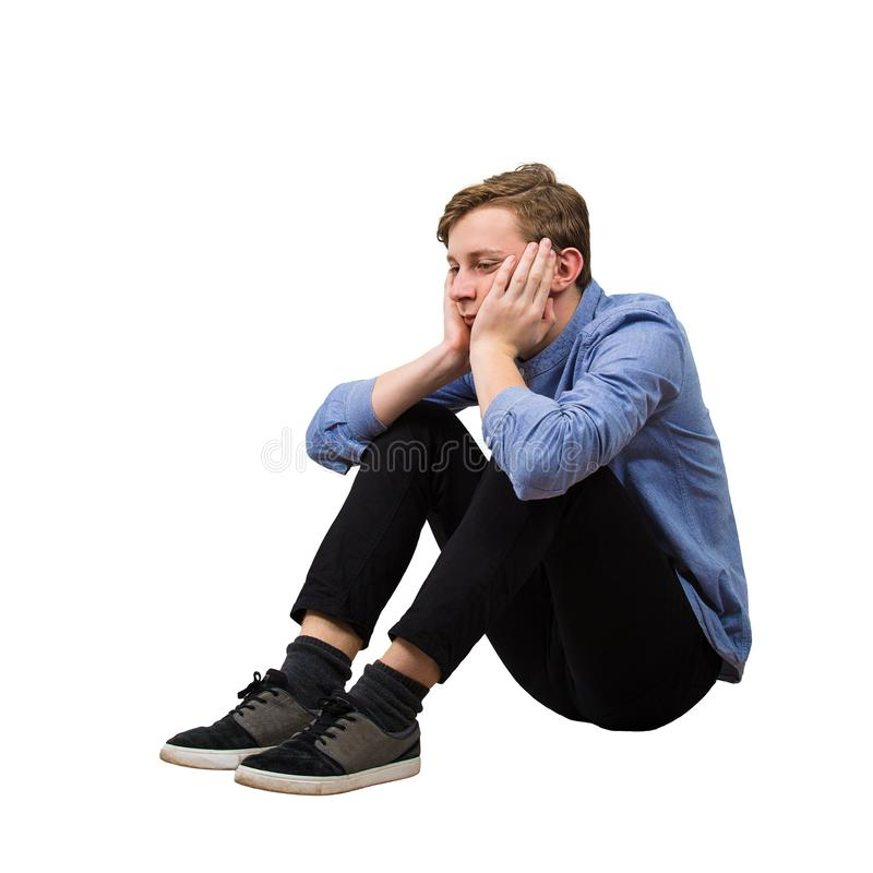 Full length side view of upset and tired boy teenager sitting on the floor keeps hands under chin looking down thoughtful isolated stock photo