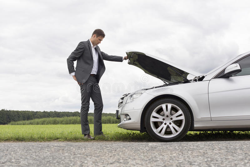 Full length side view of young businessman examining broken down car engine at countryside stock photo