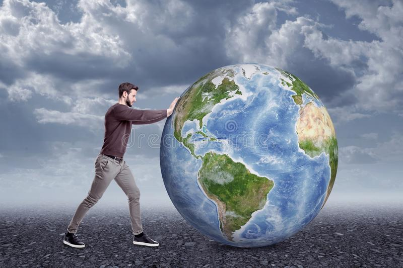 Full length side view of young man in casual clothes pushing big Earth globe on gloomy cloudy day. royalty free stock photo