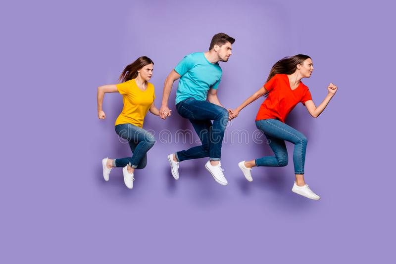 Full length size body photo of concentrated with funny facial expression group of three hipsters running away do not stock photography