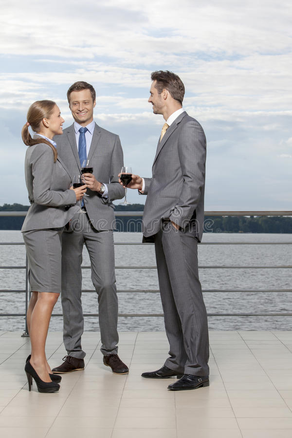 Full length of smiling businesspeople with wineglasses standing on terrace stock photo