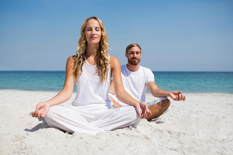 Full length of smiling couple exercising at beach royalty free stock photography