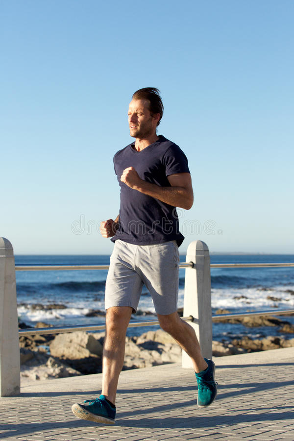 Full length sports man jogging outside by the sea. Full length portrait of sports man jogging outside by the sea stock images