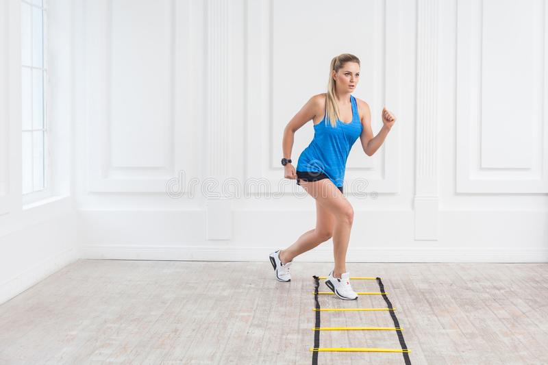 Full length of sporty beautiful young athletic blonde woman in black shorts and blue top are cardio workout with speed straps on. Floor and training on agility stock image