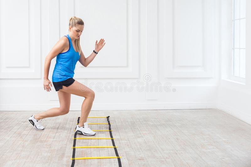 Full length of sporty beautiful young athletic blonde woman in black shorts and blue top are hard working and training on agility royalty free stock photo