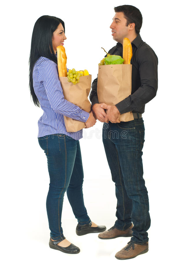 Full length of talking couple at shopping. Full length of couple holding shopping paper with food and talking together isolated on white background royalty free stock photography