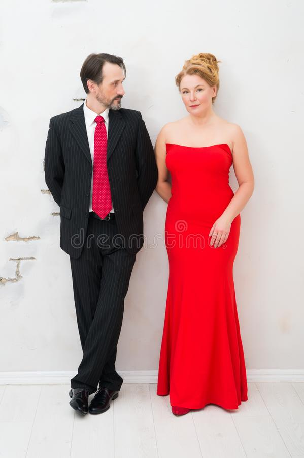 Full length of thoughtful couple in classic clothes standing against white wall stock photography