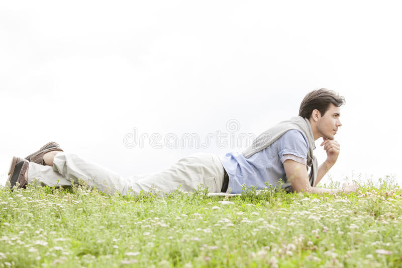 Full length of thoughtful young man lying on grass against clear sky stock image