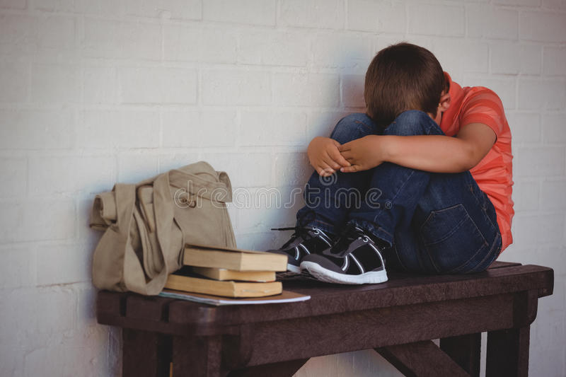 Full length of unhappy boy sitting on bench by wall stock images