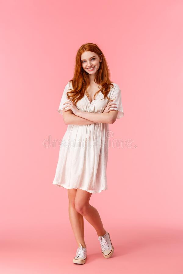 Free Full-length Vertical Shot, Feminine Beautiful Redhead Female In White Cute Dress, Cross Hands Over Chest, Smiling Lovely Royalty Free Stock Images - 170035459