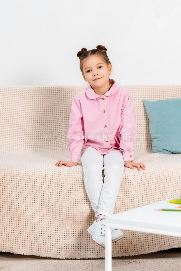 full length view of adorable little kid sitting on couch and smiling stock photography