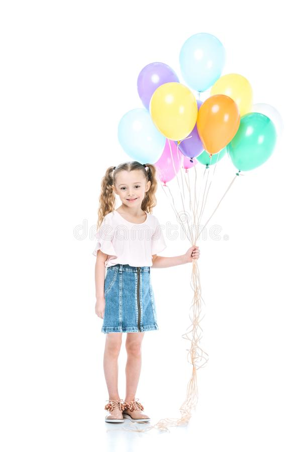 full length view of beautiful little child holding colorful balloons and smiling at camera stock photography