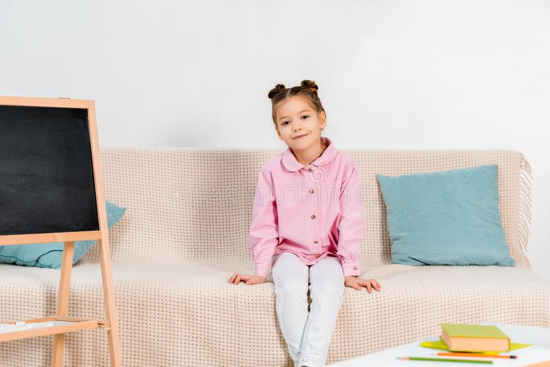 full length view of beautiful little child sitting on couch and smiling stock photography