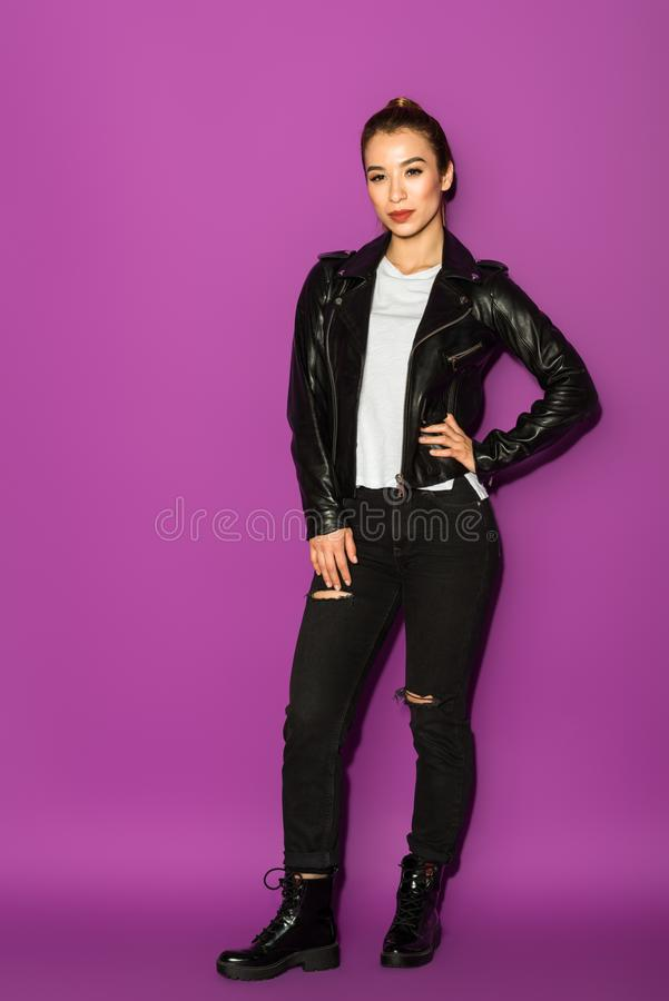 full length view of beautiful stylish asian girl in leather jacket looking at camera royalty free stock photos