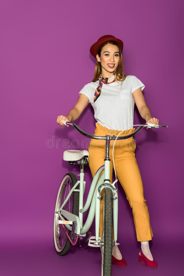 full length view of beautiful stylish asian woman standing with bicycle and smiling at camera stock image