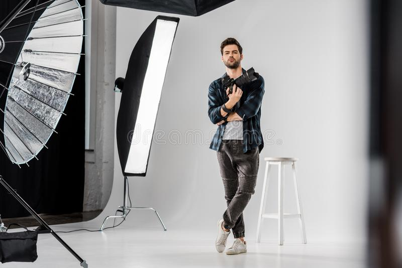 full length view of confident young photographer holding professional camera and looking at camera stock photography