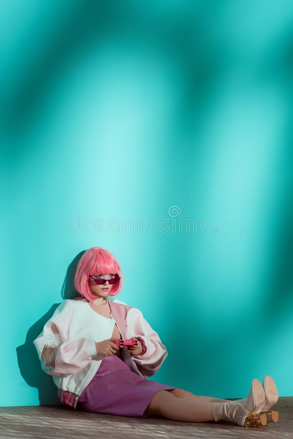 full length view of fashionable young female model in bright wig playing stock image
