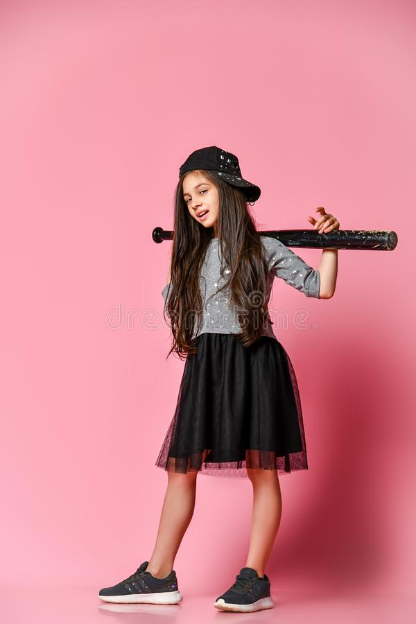 Young bright american girl with baseball bat. Full length view of a girl in a dark dress, with a mesh skirt and sneakers, wearing a cap, holding a baseball bat stock image