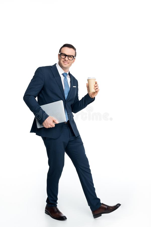 Full length view of handsome businessman holding laptop and paper cup and smiling at camera. Isolated on white royalty free stock image