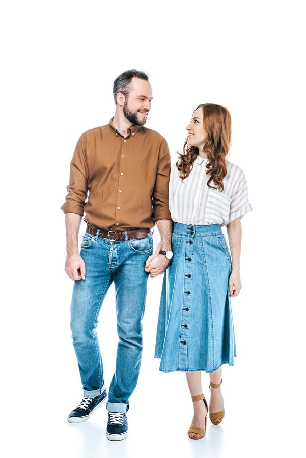full length view of happy couple holding hands and smiling each other stock photos