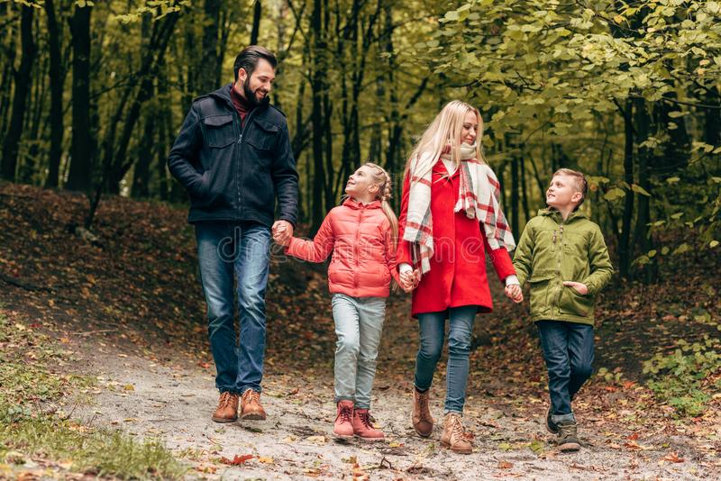 full length view of happy family holding hands and walking royalty free stock photos