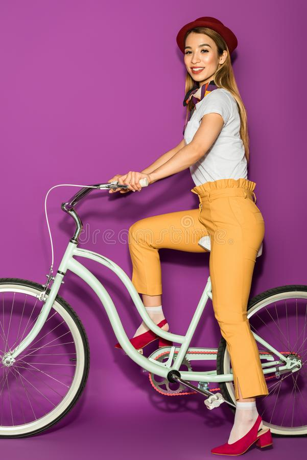 full length view of happy stylish asian girl riding bicycle and smiling at camera royalty free stock images