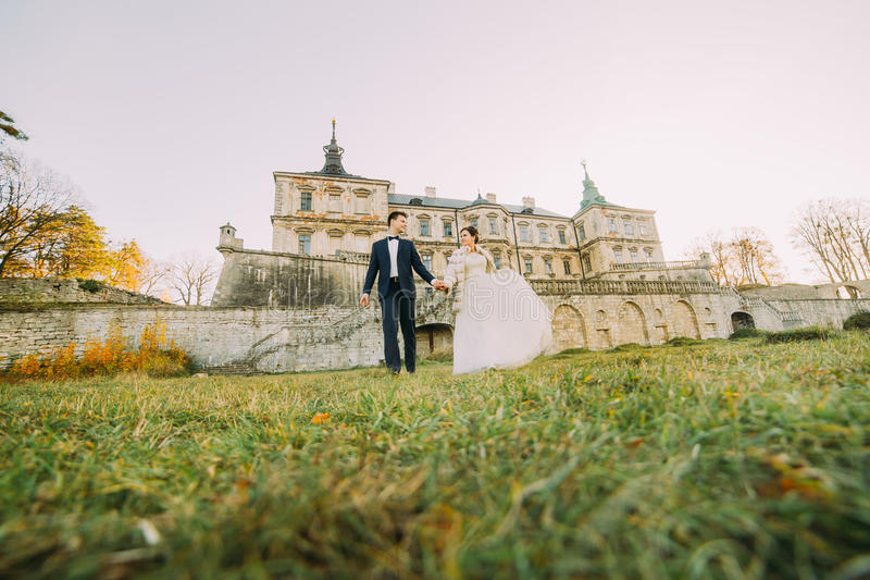 The full-length view of the newlyweds holding hands and walking in the yard of the castle. Down view stock photos