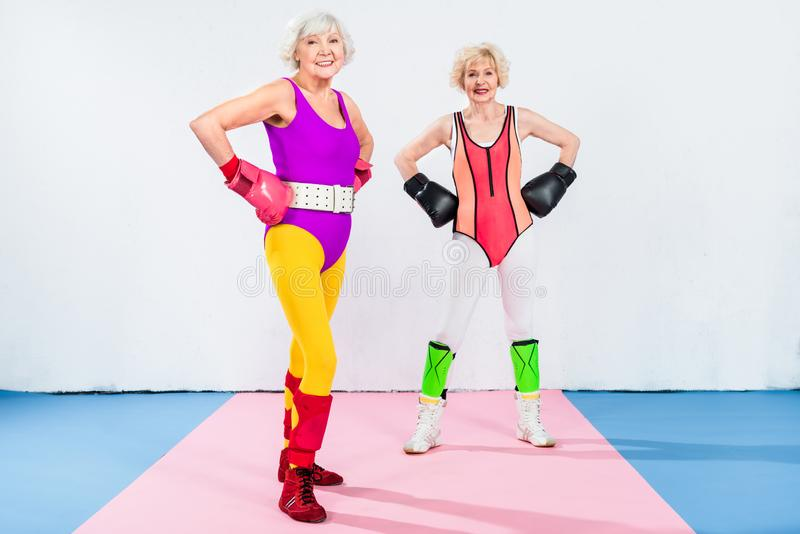 Full length view of sportive senior ladies in boxing gloves standing with hands on waist and smiling. At camera royalty free stock photos
