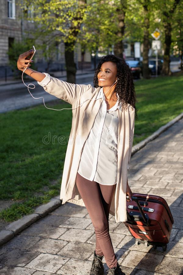 Full-length view at the stylish african woman with pretty smile holding the suitcase and taking selfie on the mobile stock photography