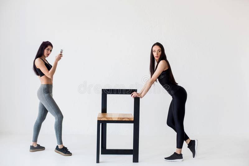 Full-length view of two charming athletic fitness women. One of them is taking photo of her friend leaning on the chair. At the white background royalty free stock images