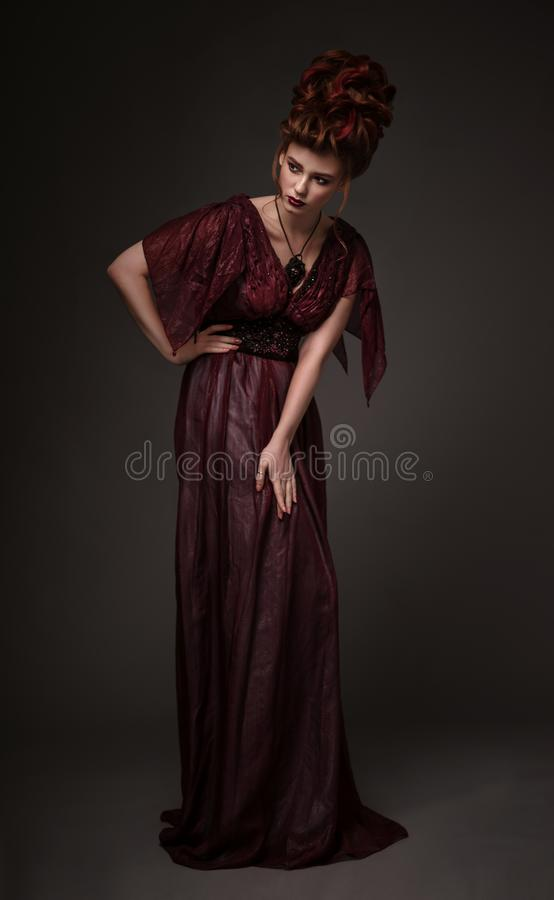 Full length view of woman with baroque hairstyle and evening maroon dress. Posing on dark background stock photos