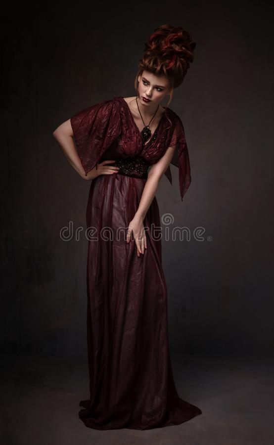 Full length view of woman with baroque hairstyle and evening maroon dress royalty free stock photos