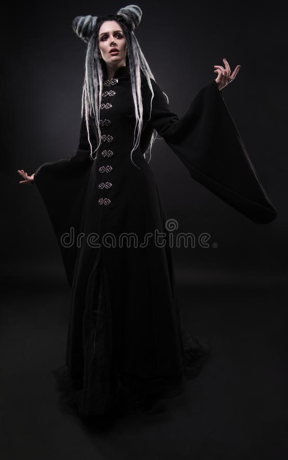 Full length view of woman with dreads wearing black gothic coat. And posing on dark background royalty free stock photography