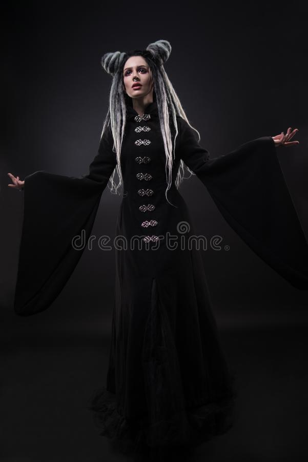 Full length view of woman with dreads wearing black gothic coat. And posing on dark background royalty free stock image