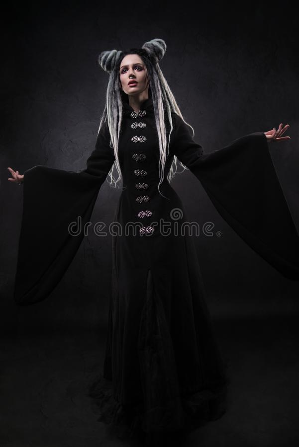Full length view of woman with dreads wearing black gothic coat. And posing on dark background royalty free stock photo