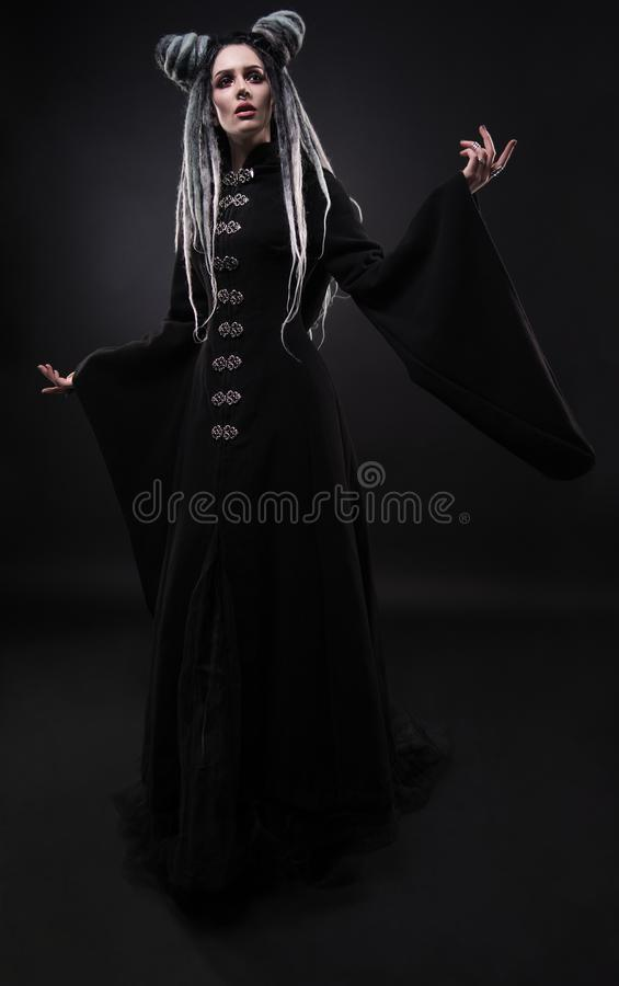 Full length view of woman with dreads wearing black gothic coat. And posing on dark background royalty free stock photos