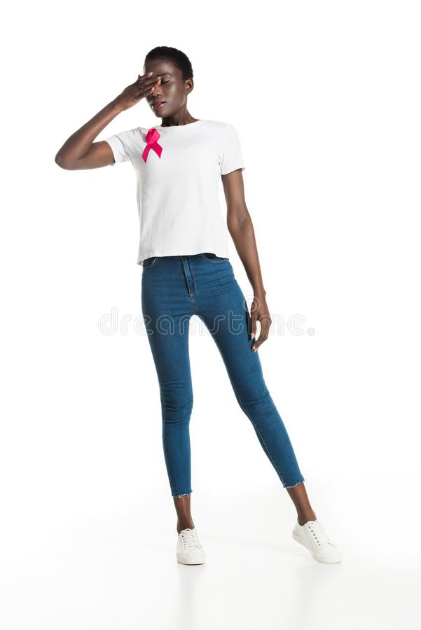 full length view of young african american woman with pink ribbon closing eyes stock photography