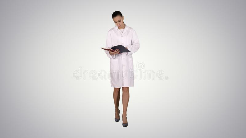 Young doctor woman reading documentation while walking on gradient background. Full length view. Young doctor woman reading documentation while walking on stock photos