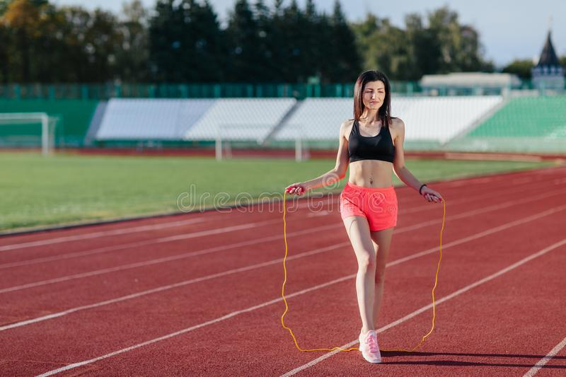 Full length view of young sport brunette woman in pink shorts and black top exercising with skipping rope on stadium royalty free stock photo