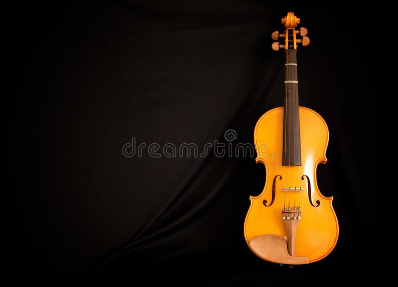Full length violin leaning on black. Full length view of violin leaning against a black background with copy space stock image