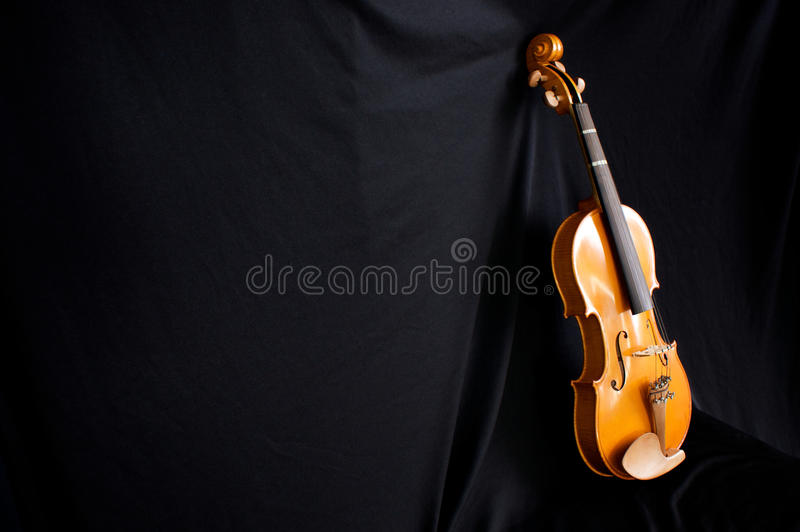 Full length violin leaning on black backdrop. Beautiful violin at an angle leaning against a black cloth background with copy space royalty free stock photography