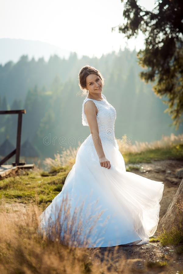 Full-length wedding shot of the beautiful smiling bride in the long dress spinning round in the forest. stock images
