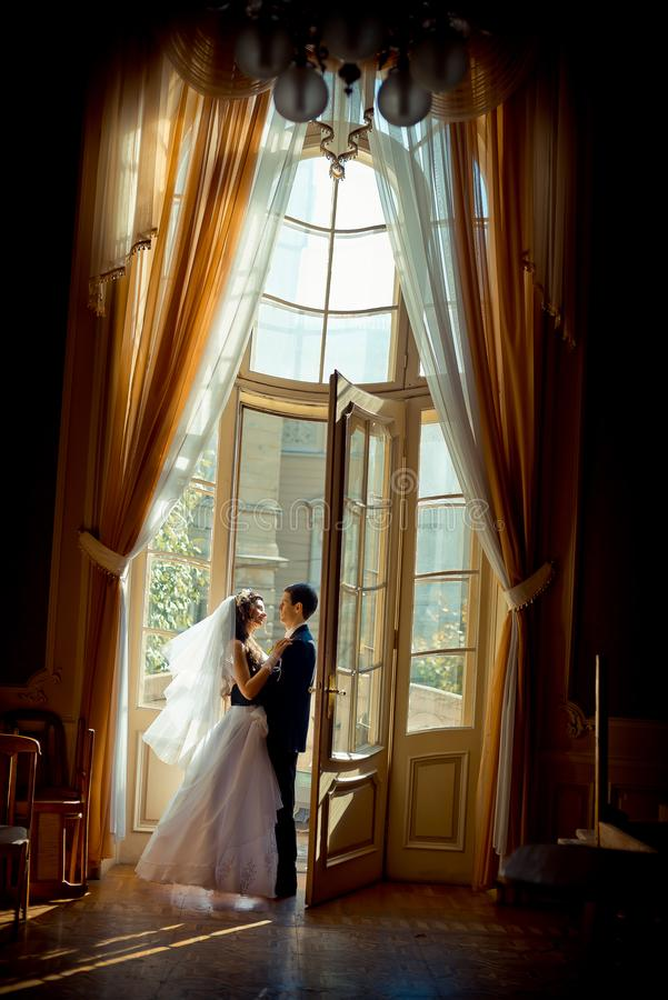 Full-length wedding shot of the stylish gorgeous newlywed couple tenderly hugging near the open window of the old rich stock images