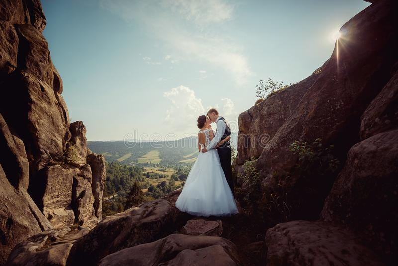 Full-length wedding shot of the stylish newlywed couple softly kissing on the mountains at the background of the royalty free stock photo