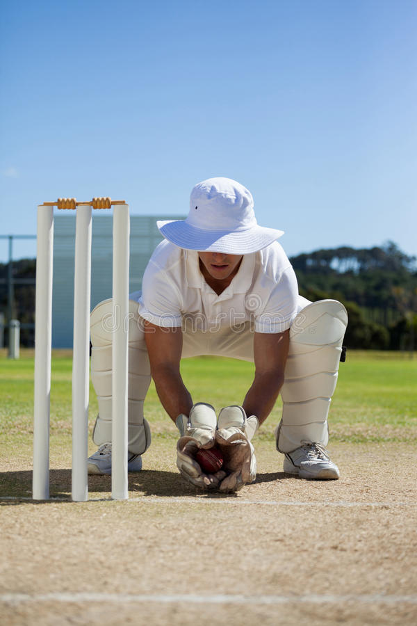 Full length of wicketkeeper holding ball behind stumps royalty free stock images