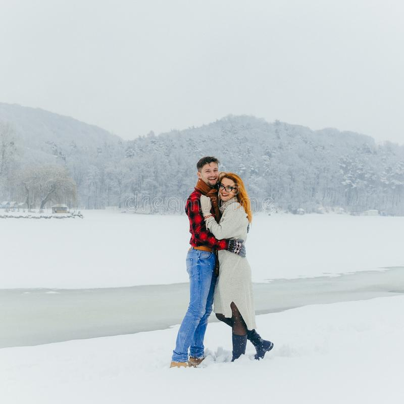 Full Length Winter Portrait Happy Laughing Smiling Loving Beautiful Couple Hugging Meadow Landscape Snowfall. royalty free stock photos