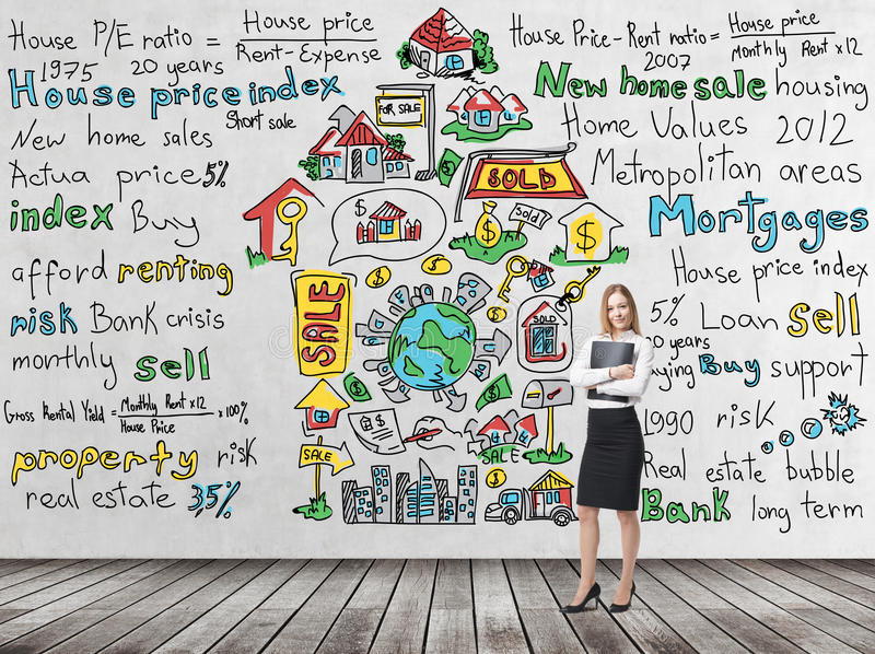 Full length woman in formal clothes holds a black folder. Colourful 'home sales' icons are drawn on the concrete wall. R. Full length beautiful woman in formal royalty free stock images