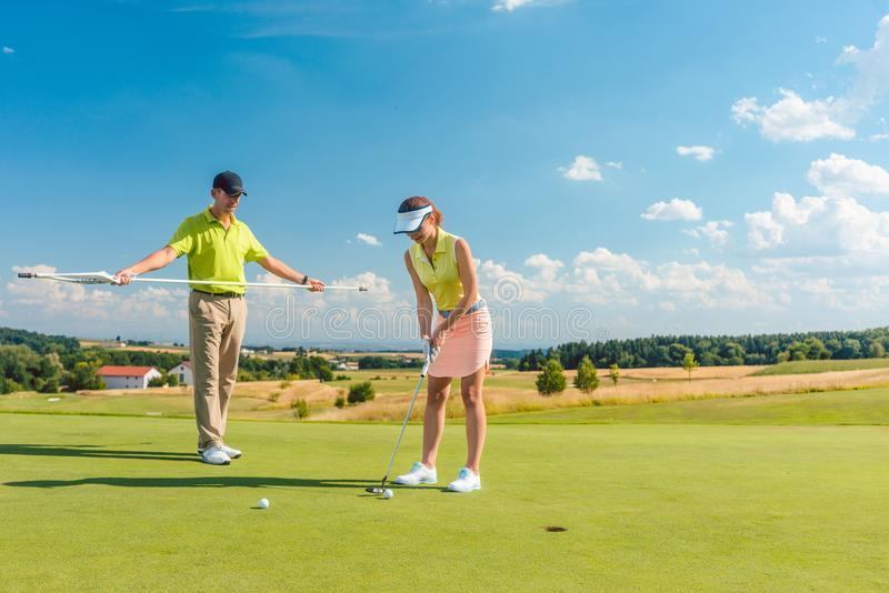 Full length of a woman playing professional golf with her male match partner royalty free stock photos