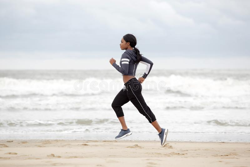 Full length young african american woman running on the beach by the water royalty free stock image